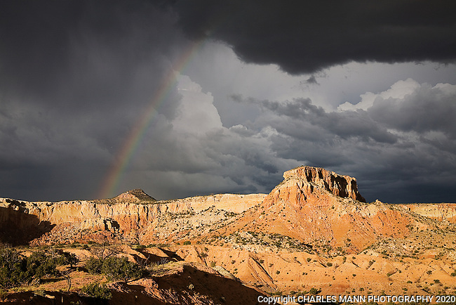 The red sandstone cliffs of Kitchen Mesa at Ghost Ranch can become dramatic on a stormy summer day at sunset when ominous cluuds are lit up by a lowering sun.