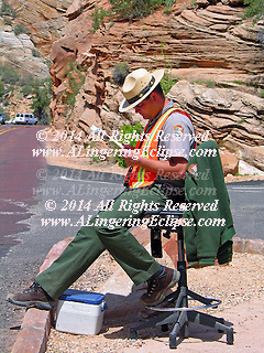 Zion National Park, Utah, USA. Photo of Park Ranger, Eric Richmond, during a break in traffic as he monitors the entrance to the tunnel through a mountain inside Zion National Park.  As Park Ranger he is entrusted with monitoring traffic for the passage through the auto tunnel in Zion National Park, is resting and reading during a break in cars. ....The fundamental purpose of the National Park Service is to conserve the scenery and the natural and historic objects and the wildlife therein and to provide for the enjoyment of the same in such manner and by such means as will leave them unimpaired for the enjoyment of future generations. To accomplish this mission, the National Park Service has employed two law enforcement resources - National Park Service protection park rangers and United States Park Police officers. Although each law enforcement entity functions independently, with distinct day to day tasks, they work cooperatively to accomplish the broad objectives of the National Park Service mission. ..The United States Park Police provide law enforcement service with a particularly urban expertise in National Park Service areas within Washington DC, San Francisco, California and New York City. Park rangers and special agents provide the criminal enforcement and much of the civil enforcement in the remainder of the NPS field areas, with emphasis on natural and cultural resource protection. ..usparks.about.com/cs/natlparkjobs/a/workparkserv_2.htm .