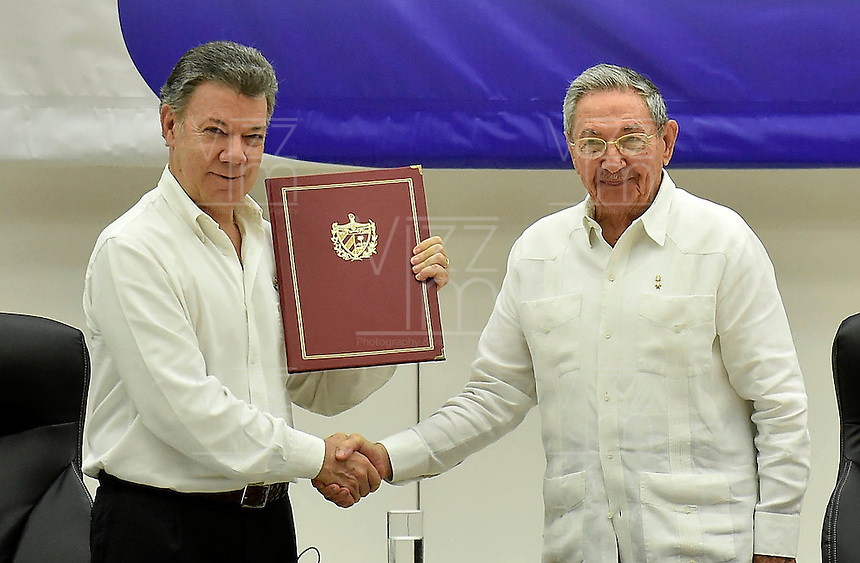 "LA HABANA - COLOMBIA, 23-06-2016 Juan Manuel Santos, presidente de Colombia, recibe de Raul Castro, presidente de Cuba, el documento firmado por Rodrigo Londoño ""Timochenko"", jefe de las Farc, hoy en La Habana durante la firma del acuerdo para el cese al fuego y de hostilidades bilateral y definitivo entre el gobierno de Colombia y la guerrilla de las Farc. El presidente de Cuba Raul Castro fue testigo como representartnte del país garante de los acuerdos. / Juan Manuel Santos, president of Colombia, receives from Raul Castro, president of Cuba, the signing document by Rodrigo Londoño ""Timochenko"", leader of Farc during the signing of the agreement of the definitive ceasefire and hostilities between Colombia Government and left guerrillas of Farc. Raul Castro, president of Cuba was the witness as representantive Country of the process. Photo: VizzorImage /  Nelson Cardenas - SIG / HANDOUT PICTURE; MANDATORY EDITORIAL USE ONLY/ NO MARKETING, NO SALES"