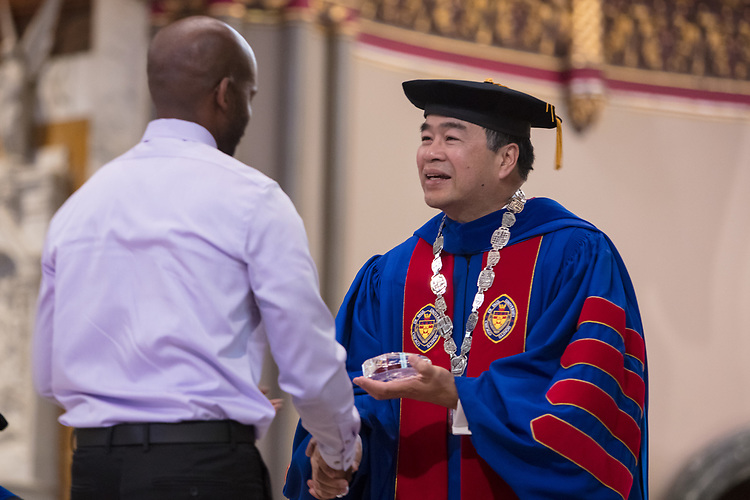 Darren Davis, associate director of Operations and Budget in the College of Science and Health, receives a Spirit of DePaul award from A. Gabriel Esteban, Ph.D., president of DePaul University, during the 120th DePaul University Convocation on Thursday, August 31, 2017, at St. Vincent de Paul Parish Church. Esteban and Marten denBoer, provost, provided remarks, and many faculty and staff were recognized through annual awards  including: Excellence in Teaching, Spirit of Inquiry, Excellence in Public Service, Vincent de Paul Professorship, Spirit of DePaul, Staff Quality Service, Gerald Paetsch Academic Advising and faculty promotion and tenure. (DePaul University/Jeff Carrion)