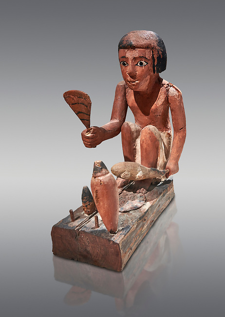 Ancient Egyptian wooden model of a man cooking a duck, New Kingdom, 11-13th Dynasty, (1980-1700 BC), Asyut. Egyptian Museum, Turin. Cat 8944. Grey background. <br /> <br /> Wooden tomb models were an Egyptian funerary custom throughout the Middle Kingdom in which wooden figurines and sets were constructed to be placed in the tombs of Egyptian royalty. These wooden models represented the work of servants, farmers, other skilled craftsman, armies, and religious rituals