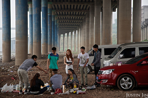 Young people enjoy a barbecue under a bridge on the outskirts of a southwestern Chinese megapolis.<br /> <br /> China is hoping by relocating farmers into cities they would start to buy food, making a break from the cycle of farmers consuming only what they produce.<br /> <br /> China is pushing ahead with a dramatic, history-making plan to move 100 million rural residents into towns and cities between 2014 and 2020 &mdash; but without a clear idea of how to pay for the gargantuan undertaking or whether the farmers involved want to move.<br />