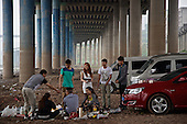 Young people enjoy a barbecue under a bridge on the outskirts of a southwestern Chinese megapolis.<br /> <br /> China is hoping by relocating farmers into cities they would start to buy food, making a break from the cycle of farmers consuming only what they produce.<br /> <br /> China is pushing ahead with a dramatic, history-making plan to move 100 million rural residents into towns and cities between 2014 and 2020 &mdash; but without a clear idea of how to pay for the gargantuan undertaking or whether the farmers involved want to move.<br /> <br /> Moving farmers to urban areas is touted as a way of changing China&rsquo;s economic structure, with growth based on domestic demand for products instead of exporting them. In theory, new urbanites mean vast new opportunities for construction firms, public transportation, utilities and appliance makers.