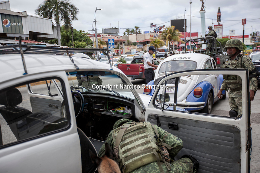June 16, 2018: Mexican army soldiers look for drugs and weapons at a flying check point set up in the touristic area of downtown Acapulco, Guerrero. A juncture of security forces, among them military, marines, federal police and local police joined under one-command to fight crime violence in the once-glamorous resort destination.