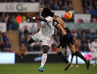 (L-R) Bafetimbi Gomis of Swansea battles for a header against Laurent Koscielny of Arsenal during the Barclays Premier League match between Swansea City and Arsenal at the Liberty Stadium, Swansea on October 31st 2015