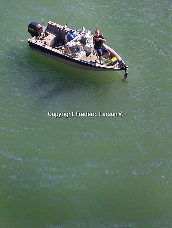 A man fish off a small boat in San Francisco Bay, California.