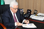 Palestinian President Mahmoud Abbas signs the credentials to adopt the name of the State of Palestine and its logo on the official transactions, in the West Bank city of Ramallah on January 3, 2012. Photo by Thaer Ganaim