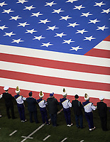 Band members and members of the armed services hold the flag during the playing of the national anthem on Salute to Service Night.