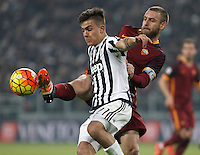 Juventus' Paulo Dybala, left, is challenged by Roma's Daniele De Rossi during the Italian Serie A football match between Juventus and Roma at Juventus Stadium.