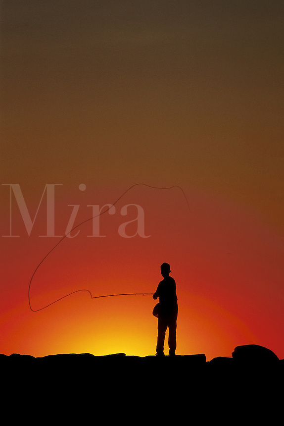 Boy fishing from a jetty at sunset, Menemsha, Martha's Vineeyard
