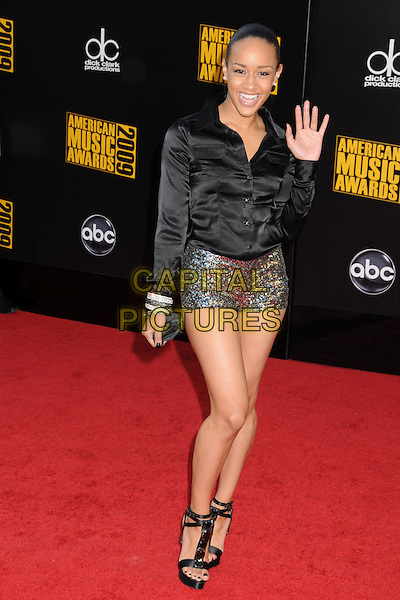 CHANI CHRISTIE. 2009 American Music Awards - Arrivals held at the Nokia Theatre L.A. Live, Los Angeles, California, USA..November 22nd, 2009.full length black shirt silk satin micro mini shorts gold silver sequins sequined AMA AMA's hand palm waving .CAP/ADM/BP.©Byron Purvis/AdMedia/Capital Pictures.