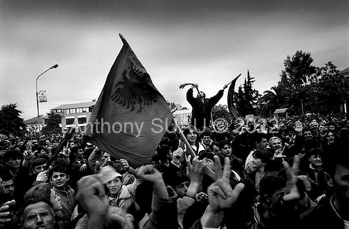 Fier, Albania<br /> February 1997<br /> <br /> Demonstrators march through the streets demanding that the government step down. The man atop the crowd waves an Albanian flag and swings a leek (the main food of the poor Albanian).