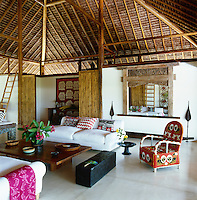 The living room is furnished with a beaded African chair and comfortable sofas