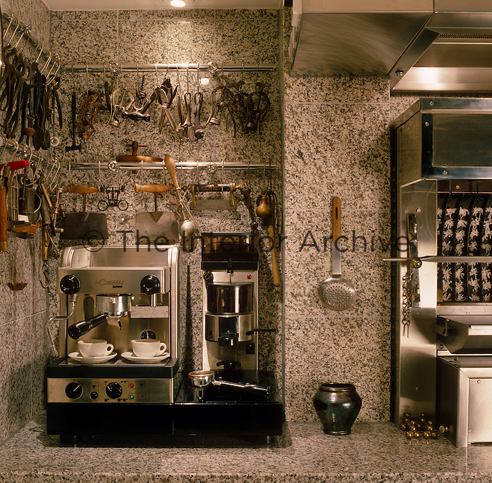 A collection of kitchen utensils and tools hangs on stainless steel racks above a coffee maker at one side of the grill