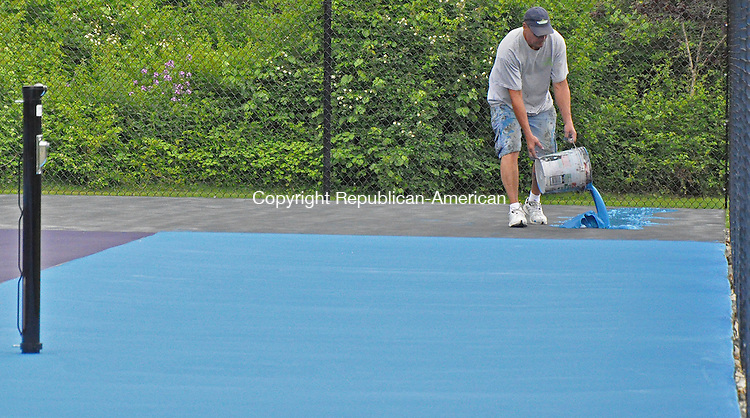 KENT, CT – 06 June 2014 - 060614LMW02–Jack Kinne of Hinding Tennis Courts pours blue paint Friday afternoon that was later spread on the surface of the new tennis courts at Kent Common Park. The open house planned for today has been moved back two weeks to June 21. Lynn Mellis Worthington Republican-American