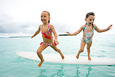 INDONESIA, Mentawai Islands, Kandui Resort, girls jumping off of a surfboard into the Indian Ocean