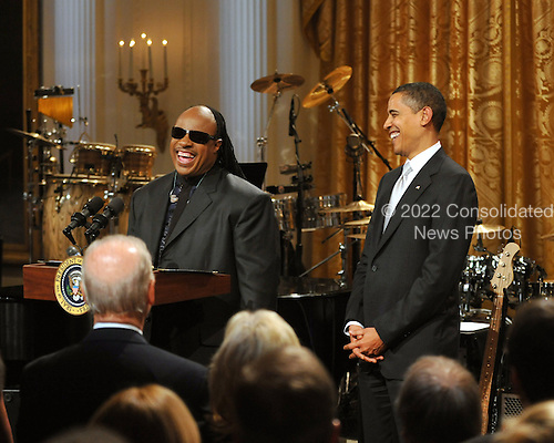 """Washington, D.C. - February 25, 2009 -- Stevie Wonder makes remarks as United States President Barack Obama looks on during the taping of """"Stevie Wonder In Performance at the White House: The Library of Congress Gershwin Prize"""" to showcase an evening of celebration at the White House in honor of musician Stevie Wonder's receipt of the Library of Congress Gershwin Prize for Popular Song in the East Room of the White House in Washington, D.C. on Wednesday, February 25, 2009..Credit: Ron Sachs / Pool via CNP"""