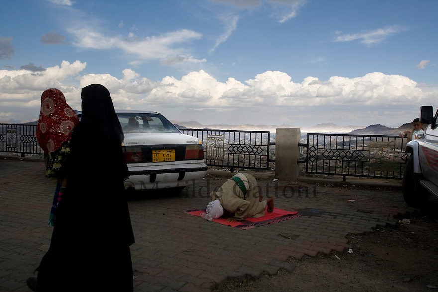 Yemen - Sana'a - Old man praying after having washed arms and legs follwoing the rules of islam.Yemen's economy depends heavily on oil production, and its government receives the vast majority of its revenue from oil taxes. Yet analysts predict that the country's petroleum output, which has declined over the last seven years, will fall to zero by 2017. The government has done little to plan for its post-oil future. Yemen's population, already the poorest on the Arabian peninsula and with an unemployment rate of 35%, is expected to double by 2035..The trends will exacerbate large and growing environmental problems, including the exhaustion of Yemen's groundwater resources. Given that a full 90% of the country's water is used for agriculture, this trend portends disaster..Sanaa's well are expected to dry out by 2015, partly due to illegal drilling, partly because 40% of the city's water is diverted for qat production, and partly because conservation rules are difficult to enforce. Only 20% of the houses receive water, the other 80% has to collect it from pumps and wells. 15% of the urban population only uses bottled water as its primary drinking water source and that is why Yemen has one of the highest world mortality rate, most of the diseases being related to water..
