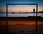 A barge sitting in English Bay framed by an outdoor shower during sunset.