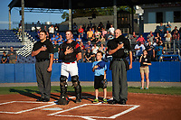 Batavia Muckdogs catcher David Gauntt (7) stands with umpires John Boccio (left) and Matt Baldwin (right) during the national anthem before a game against the Tri-City ValleyCats on July 15, 2017 at Dwyer Stadium in Batavia, New York.  Tri-City defeated Batavia 5-4.  (Mike Janes/Four Seam Images)