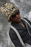 """KINSHASA, DEMOCRATIC REPUBLIC OF CONGO - FEBRUARY 10: A Sapeur poses for a portrait with his designer label clothes while paying his respects to Stervos Nyarcos, the founder of the .kitendi religion. which means clothing in local language Lingala. Nyarcos was known as the leader of the Sape movement, at Gombe cemetery on February 10, 2016 in Kinshasa, DRC. The word Sapeur comes from SAPE, a French acronym for Société des Ambianceurs et Persons Élégants. or Society of Revellers and Elegant People. and it also means, .to dress with elegance and style"""". Most of the young Sapeurs are unemployed, poor and live in harsh conditions in Kinshasa, a city of about 10 million people. For many of them being a Sapeur means they can escape their daily struggles and dress like fashionable Europeans. Many hustle to build up their expensive collections. Most Sapeurs could never afford to visit Paris, and usually relatives send or bring clothes back to Kinshasa. (Photo by Per-Anders Pettersson)"""