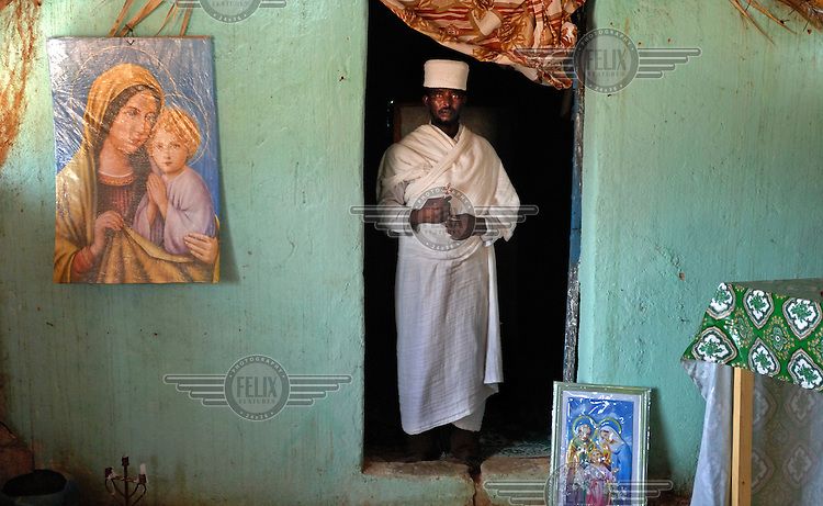 Priest Kewani stands inside St. Mary's Coptic church. A picture of the Virgin Mary holding Jesus is visible on the wall.