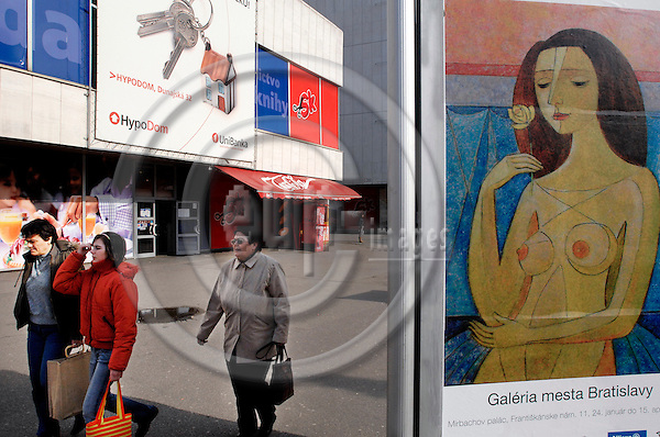 """BRATISLAVA - SLOVAKIA 9. MARCH 2007 -- Street scene from Bratislava. Three women passes an advertisement for an art exhibition with an bank advertisement in the back    -- PHOTO: GORM K. GAARE / EUP & IMAGES..This image is delivered according to terms set out in """"Terms - Prices & Terms"""". (Please see www.eup-images.com for more details)"""