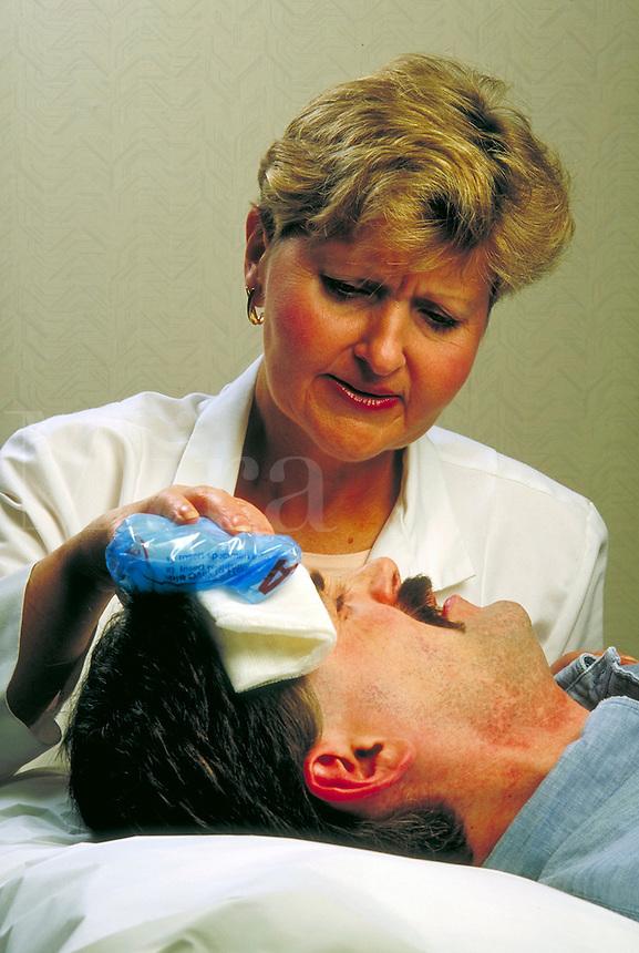 Nurse applies cold compress to head injury patient.<br />