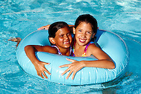 Girls playing with a float tube in a swimming pool.