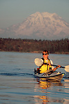 Woman sea kayaker paddling toward camera in Nisqually Reach on Puget Sound with Mount Rainier dominant in the background.