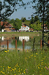 White home reflected in Forggensee lake close to Neuschwansein castle. Bavaria, South Germany.