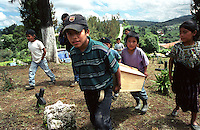 Young children carry a coffin with the remains of a family member who died and was buried in a clandestine grave, during the civil war.  The remains are being returned for burial within the family's community. El Quiche, Guatemala, August 2001.