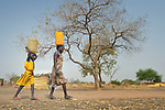 With help from her 8-year old daughter Atap, Atouc Dut carries home water from a well in Malek Miir, a village in South Sudan's Lol State where a persistent drought has destroyed crops and left people hungry. A local partner of Christian Aid, a member of the ACT Alliance, drilled the well and has provided food vouchers to hungry families, including Dut and her husband and four children. With food vouchers instead of bulk food, beneficiaries were able to buy the exact food they wanted, while at the same time supporting local traders and markets.