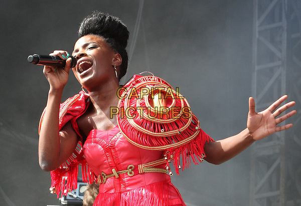 Shingai Shoniwa.THE NOISETTES perform at Day Two V Festival at Hylands Park, Chelmsford, Essex, England..August 21st, 2011.stage concert live gig performance music half length red pink hand arm top jacket epaulettes shoulder pads gold fringed tassels singing hair up bun .CAP/ROS.©Steve Ross/Capital Pictures