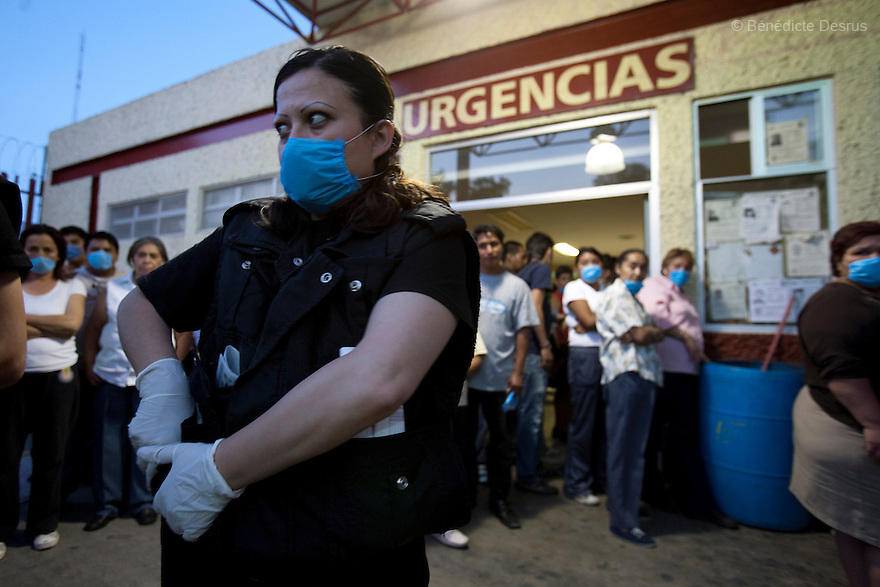 28 april 2009 - Mexico City, Mexico - Police onload a prisoner at the General Hospital of Iztapalapa. Most  of the people wait at the hospital to be checked for Swine FLu like symptoms. They wear surgical masks to protect themselves from the swine Flu. Photo credit: Benedicte Desrus / Sipa Press
