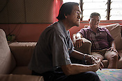 51 year old Goh Kuam Boon, a former pig farmer and a  survivor of the Nipah virus seen with a friend, Thomas Wang (left) in his house in Bukit Pelandok in Nageri Sembilan, Malaysia on October 16th, 2016. <br /> In September 1998, a virus among pig farmers (associated with a high mortality rate) was first reported in the state of Perak in Malaysia. Dr. Chua investigated and discovered the virus and it was later named, Nipah Virus. The outbreak in Malaysia was controlled through the culling of &gt;1 million pigs.
