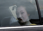Geisha looks at photographer as she  leaves for her appointment by hired car in the Gion District of Kyoto.