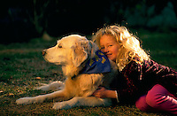 Young girl hugging her old golden retriever.
