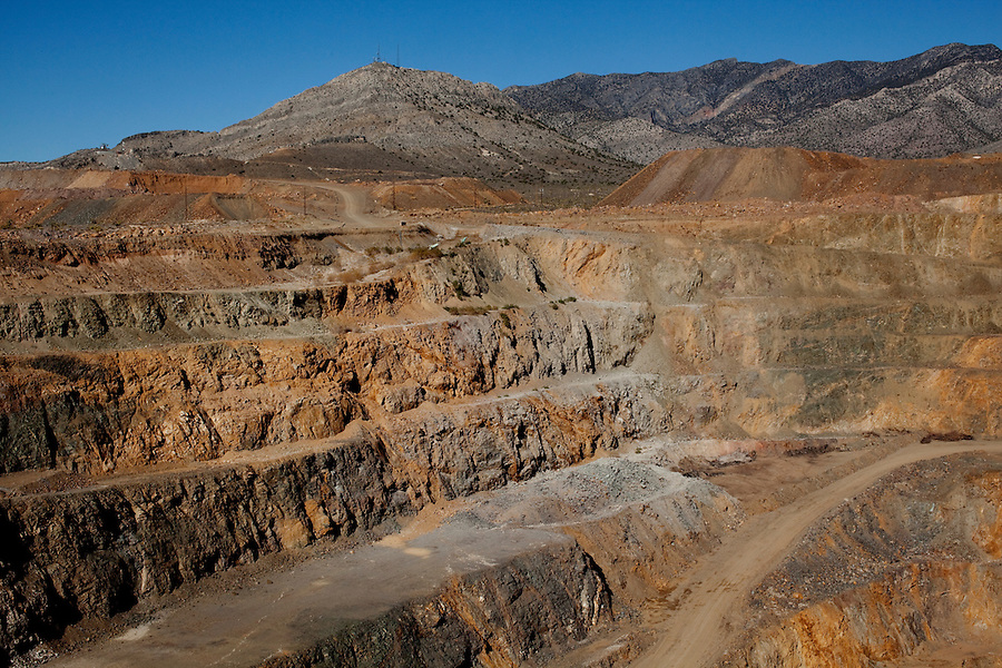 "Mountain Pass, California, November 15, 2010 - A view of the open-air mine at Mountain Pass, owned by Molycorp Minerals, which mines rare earth elements. According to Scott Honan, an Environmental Manager for Molycorp, the grey rock in unusable minerals, while the brown and pink rock contains rare earth minerals. ""When we resume mining operations, we will be able to mine 2 tons of earth per day, with about an 8% yield of rare earth,"" Honan added. Rare earth elements - there are 17 in all - are crucial for many current technologies, including mobile phones, wind turbines, hybrid cars, laptops and military hardware, such as Army tank navigation systems and Navy radars. Uranium prospectors discovered the mine at Mountain Pass in 1949 and it became the dominant producer of rare earth elements until the 1990s when pressure from other producers began to drive prices down. That along with a number of leaks of radioactive water during transmission into a evaporation lake 13 miles away and state regulators delaying operating permits forced the mines closure in 2002. Though mining ceased, some processing of already mined elements continued. Molycorp was purchased by Unocal in the 1970s, which in turn was purchased from Chevron. In 2008 it's long-time chief executive, Mark A Smith, purchased in from Chevron with the help of several private equity firms. The company raised $500 million in an effort to reopen the mine, which will include expanding and modernizing the current facilities as well as incorporating newer technologies to make mining the radioactive material more environmentally safe and adding a natural gas power plant to help reduce its need to buy more expensive and less reliable energy from Los Angeles.  ."