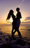 Young couple as a silhoette in the sunrise on the beach in Florida, USA