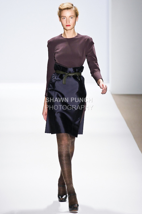 Laura Blokhina walks runway in a long sleeve red titanium hi-tech lycra dress with deep blue silk-mikado overskirt, brown hand-knitted ombre tights, and green leather belt, by Joaquin Trias, for his Trias Autumn Winter 2010, Vertical Strength collection, during the Mercedes-Bens Fashion Week Fall 2010.