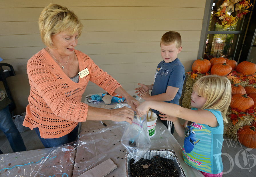 NWA Democrat-Gazette/BEN GOFF @NWABENGOFF<br /> Cathy Patterson, Hobbs State Park volunteer, helps Evan Carlson, 8, and sister Anastacia Carlson, 5, of Rudy make pine cone bird feeders on Sunday Oct. 2, 2016 duirng the annual Fall Festival at Hobbs State Park - Conservation Area near Rogers. The event featured a variety of family-friendly nature and old-time activities at the park's visitors center and Historic Van Winkle Hollow area.