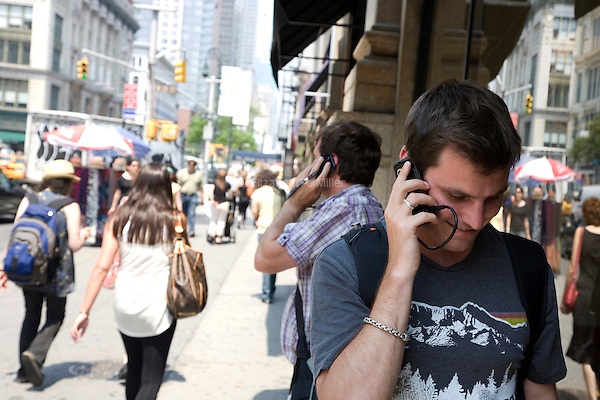 "A man walks down 6th Avenue in New York City, talking on his cell phone on June 1st, 2011.  The World Health Organization (WHO) has listed mobile phone use in the same ""carcinogenic hazard"" category as lead, engine exhaust, and chloroform, making use of cell phones a possible cancer risk."