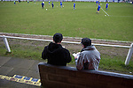 Glossop North End 0 Barnoldswick Town 1, 19/02/2011. Surrey Street, North West Counties League Premier Division. Two spectators reading the matchday programme in front of the main stand at Glossop North End's Surrey Street ground before the club's game with Barnoldswick Town in the Vodkat North West Counties League premier division. The visitors won the match by one goal to nil watched by a crowd of 203 spectators. Glossop North End celebrated their 125th anniversary in 2011 and were once members of the Football League in England, spending one season in the top division in 1899-00. Photo by Colin McPherson.