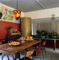 A kitchen/dining space with a grey-painted wood ceiling and red, grey and white painted walls. The room is furnished with an interesting mix of styles such as a bow fronted corner cupboard, an assortment of simple school chairs and a wood dining table. A collection of Vallauris pottery is displayed against the far wall