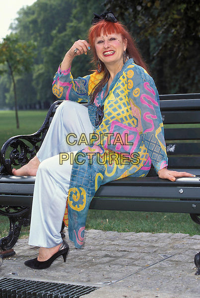 ZANDRA RHODES.Ref: 3254.full length sitting blue yellow pink pattern coat.www.capitalpictures.com.sales@capitalpictures.com.©Capital Pictures.