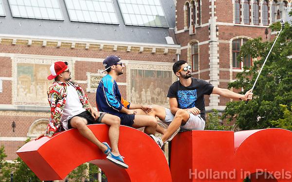 Nederand Amsterdam. Toeristen zitten op de I Amsterdam letters op het Museumplein en maken een selfie