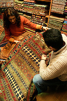 CUSTOMER BUYING TEXTILES AT THE GRAND BAZAAR, ISTANBUL, TURKEY