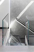 Cantilevered glass treads and a metal handrail have been inserted into the concrete stairwell wall