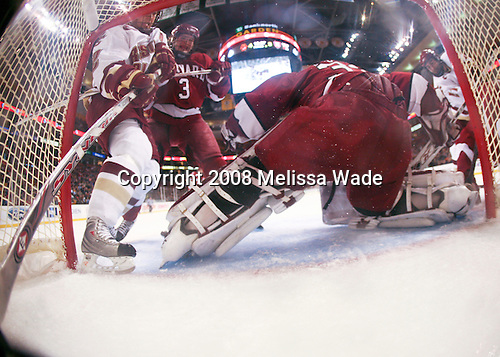 Alex Biega (Harvard 3) pushes Dan Bertram (BC 22) into the crossbar while Kyle Richter (Harvard 33) makes a save on Benn Ferriero (BC 21). The Boston College Eagles defeated the Harvard University Crimson 6-5 in overtime on Monday, February 11, 2008, to win the 2008 Beanpot at the TD Banknorth Garden in Boston, Massachusetts.